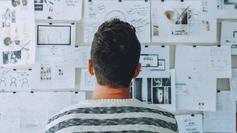 壁に貼った資料を眺めて考え込む男性