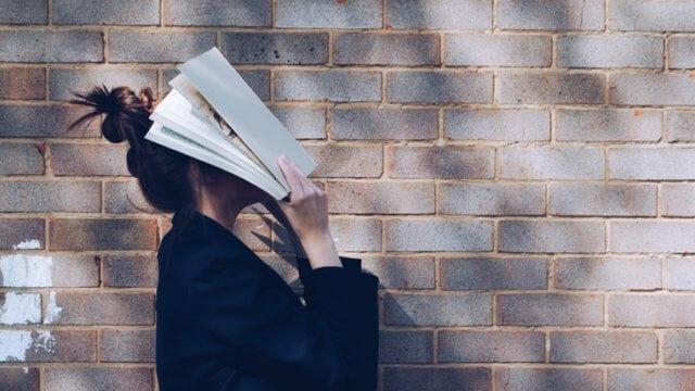 本を顔に当てて悩む女性