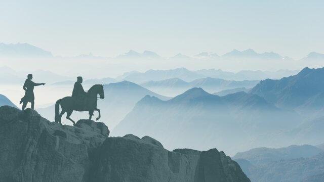 険しい山々を馬を率いて進む2人