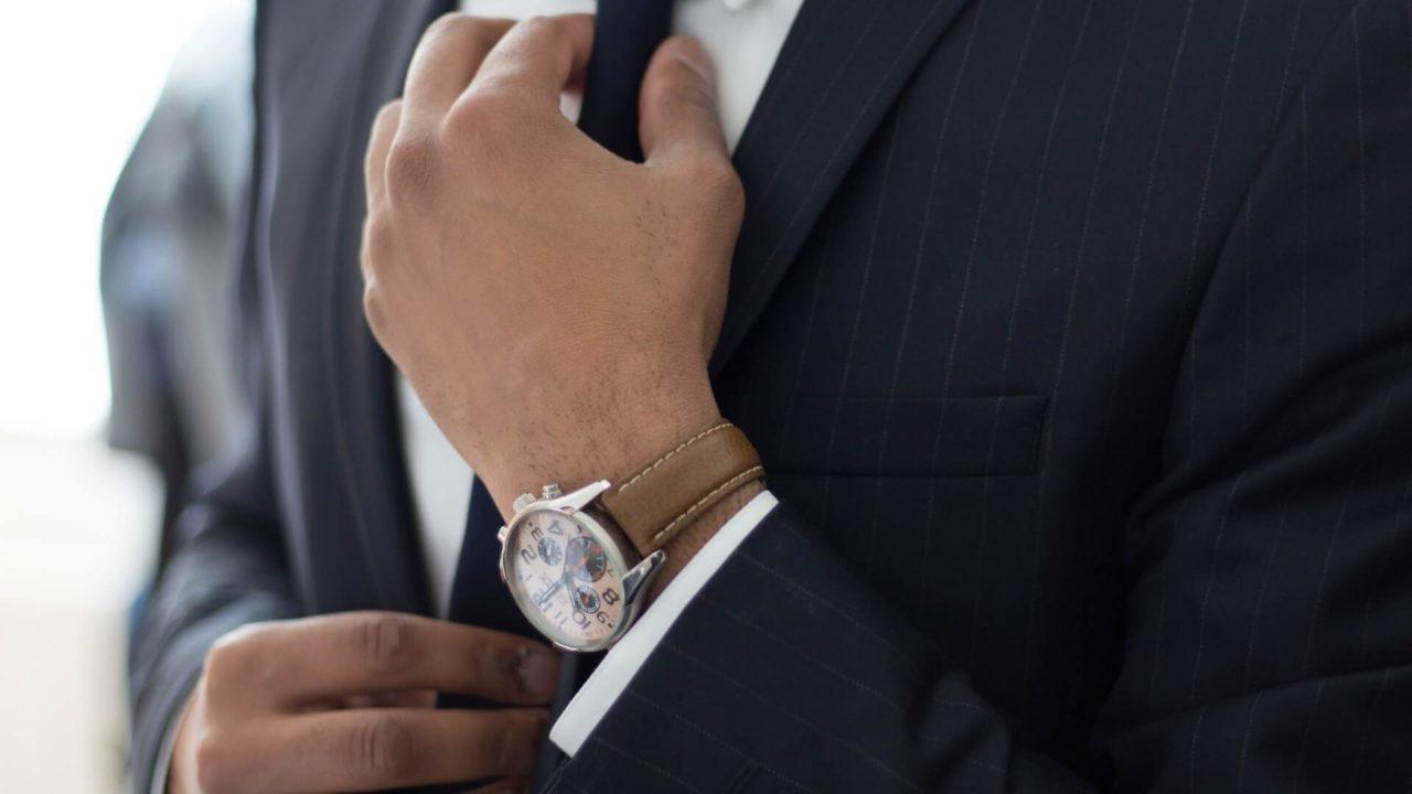 スーツを着てネクタイを締める