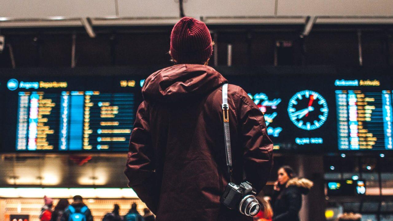 空港の掲示板を見る男性